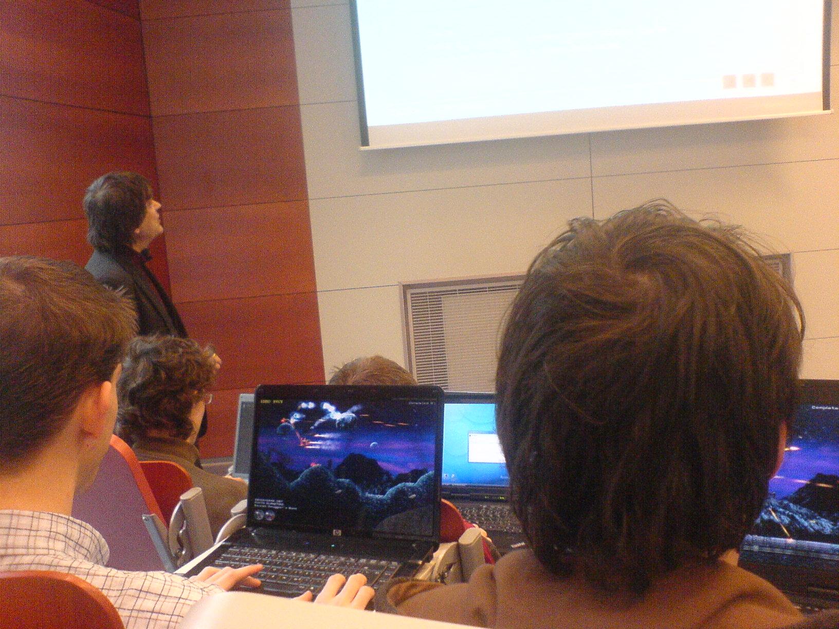Přednáška - tvorba elektrotechnické dokumentace. Dva studenti hrají hru, prakticky vedle přednášejícího.