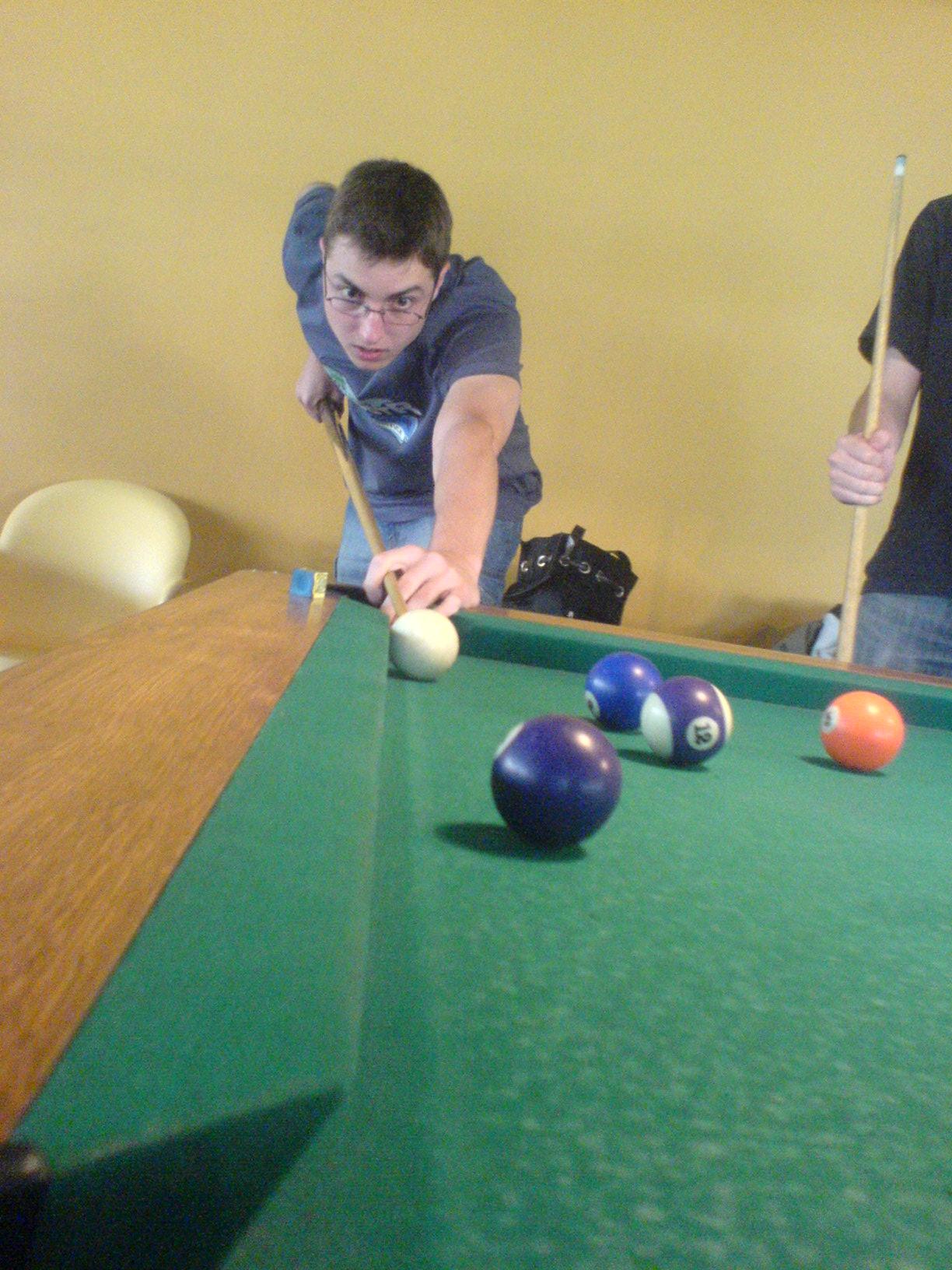 Pavel hraje kulečník v herně na Strahově.